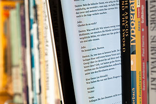 An iPad with text sits between ordinary books in a bookshelf. Maximilian Schönherr
