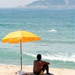 Man sitting under beach umbrella, Photo by Johntex, 2006. Source : Wikimedia Commons.